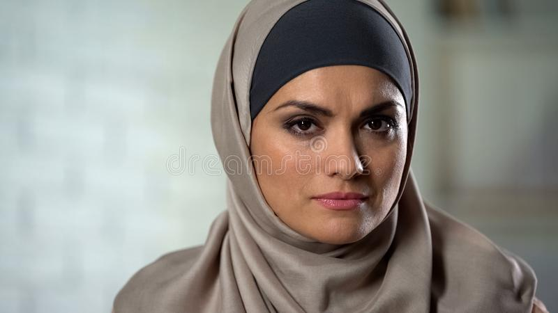 哀伤地看在照相机的hijab的沮丧的女性,感觉被伤害的,被虐待的妇女 免版税库存图片