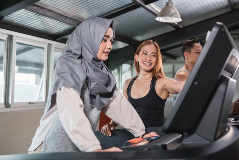Hijab asiático novo das mulheres corrido na escada rolante imagem de stock