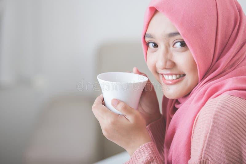 Hijab d'uso della donna abbastanza asiatica che gode del caffè fotografie stock libere da diritti