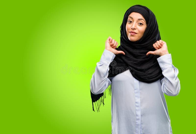 Hijab d'uso della giovane donna araba isolato sopra fondo verde fotografia stock