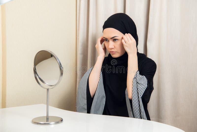 Hijab d'uso della giovane donna attraente a casa Hijab d'uso della bella ragazza musulmana fotografia stock libera da diritti