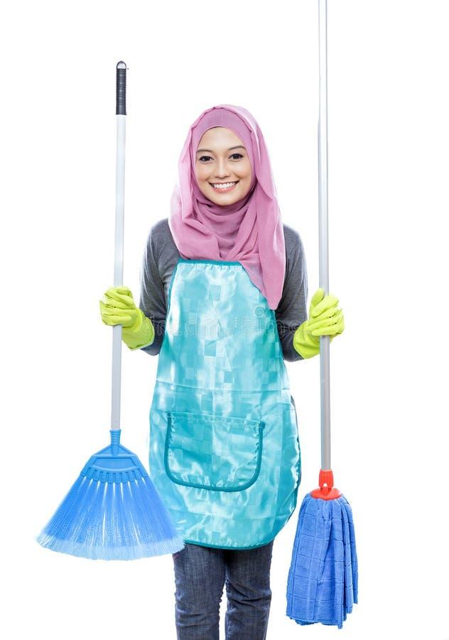 Hijab de port de femme au foyer tenant le balai et le balai image stock