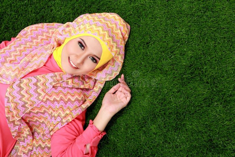 Hijab de port de jeune fille musulmane se trouvant sur l'herbe avec l'espace de copie photographie stock libre de droits
