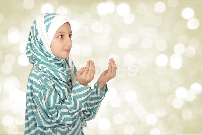 Hijab de port de petite fille musulmane mignonne - fabrication du duaa priant à images libres de droits