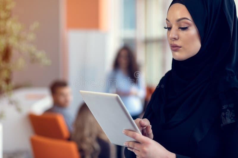 Hijab de port de jolie femme devant la recherche et faire d'ordinateur portable le travail de bureau, les affaires, les finances  images libres de droits