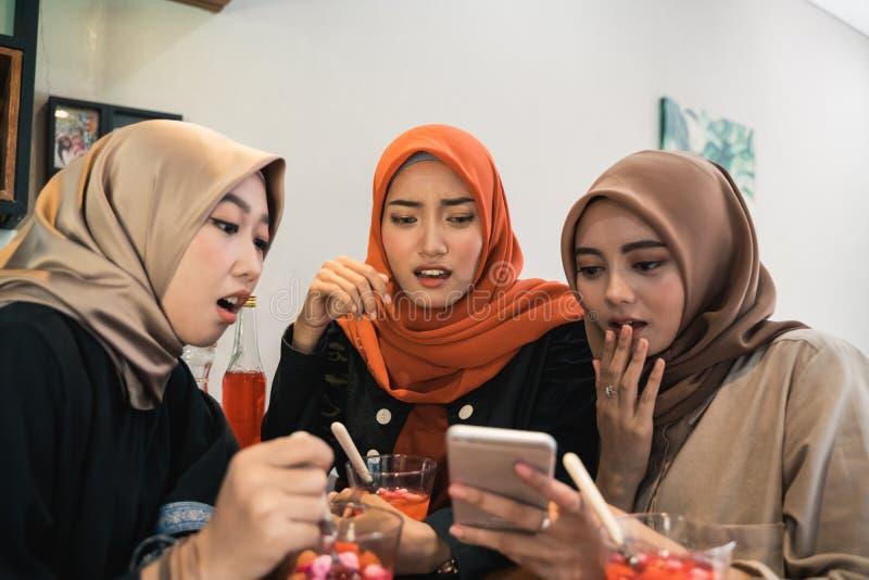 Hijab kvinnor och v?nner som h?ller ?gonen p? den chockade videoen p? en smartphone och fotografering för bildbyråer