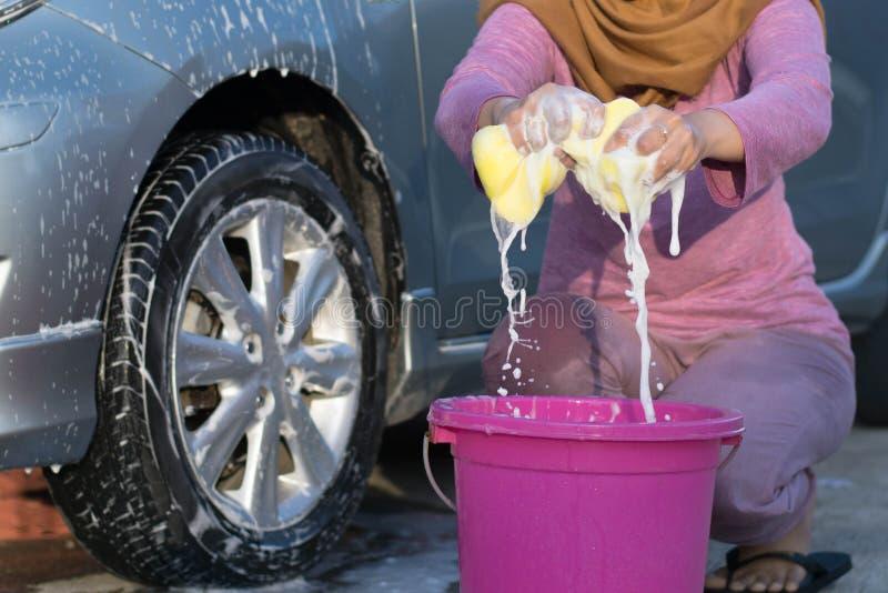 Hijab kvinnor pressar den gula svampen, medan tvätta bilen arkivbild
