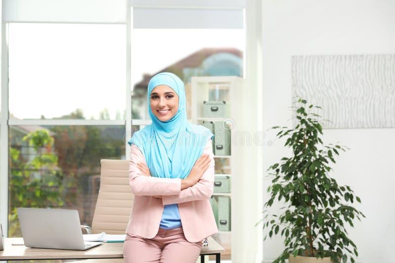 Hijab que lleva de la empresaria musulmán moderna cerca de la tabla imagenes de archivo