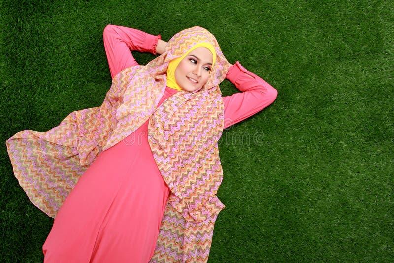 Hijab que lleva de la muchacha musulmán joven que miente en hierba y que mira el co imagen de archivo libre de regalías