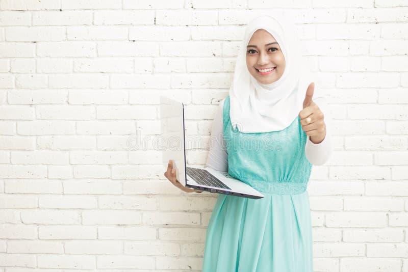 hijab que lleva de la mujer asiática que sostiene el ordenador portátil y que da los pulgares para arriba fotos de archivo libres de regalías