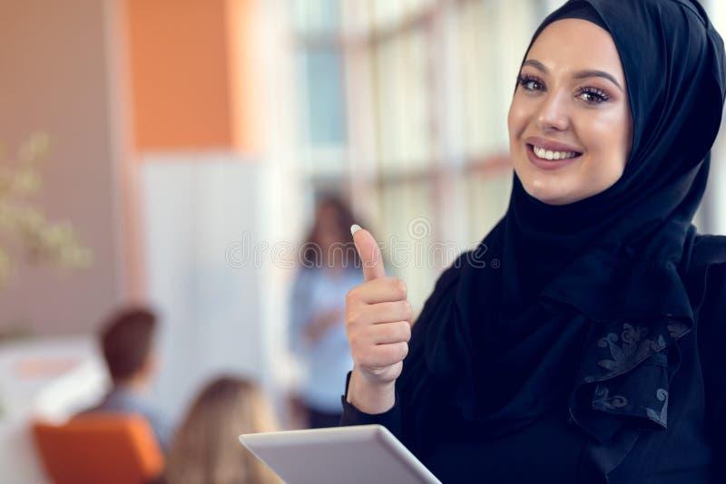 Hijab que lleva de la mujer bonita delante de la búsqueda y de hacer del ordenador portátil el trabajo de oficina, el negocio, fi imagen de archivo libre de regalías