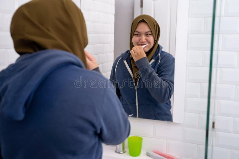 Hijab que lleva de la mujer cepillar sus dientes imagenes de archivo