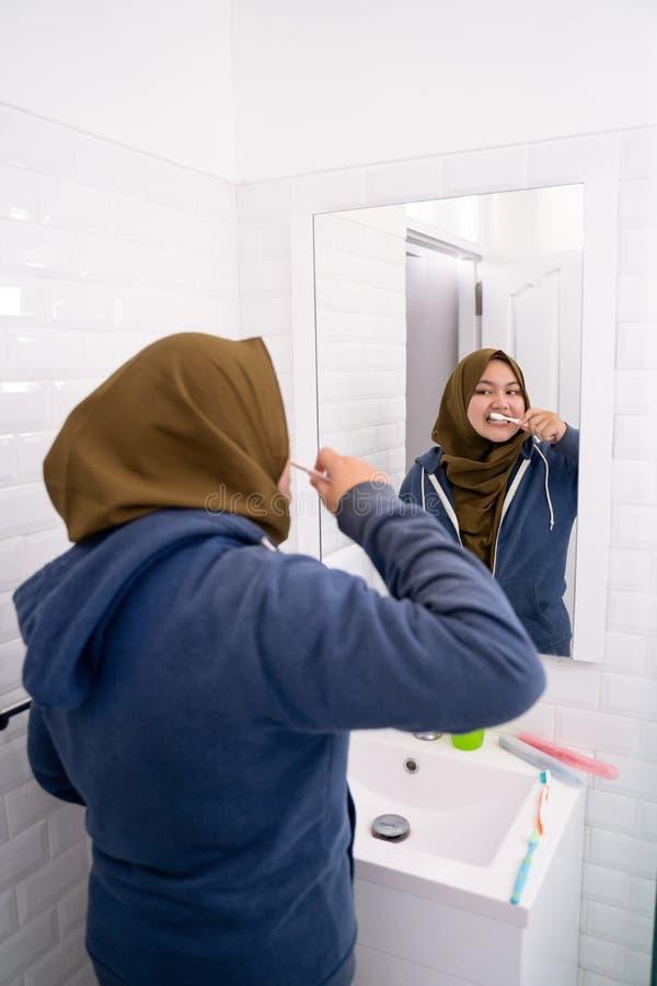 Hijab que lleva de la mujer cepillar sus dientes fotografía de archivo libre de regalías