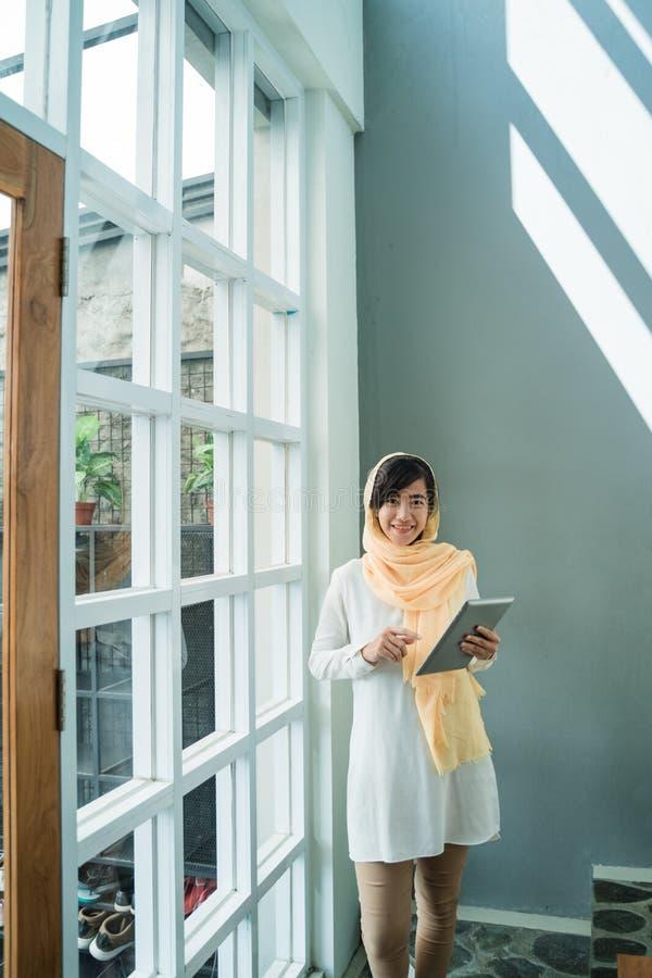 Hijab que lleva de la mujer musulmán usando la PC de la tableta imagen de archivo