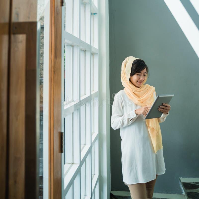 Hijab que lleva de la mujer musulm?n usando la PC de la tableta imágenes de archivo libres de regalías