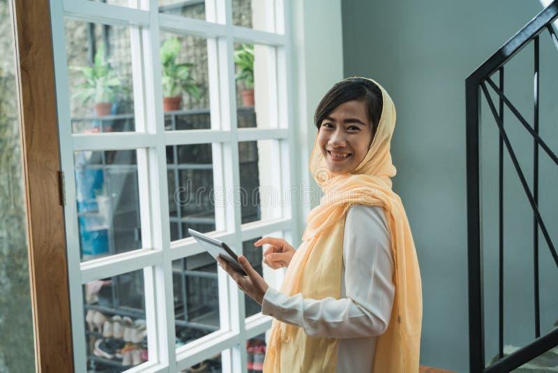 Hijab que lleva de la mujer musulm?n usando la PC de la tableta imagenes de archivo