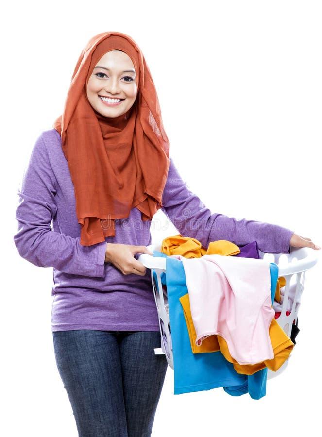 Hijab que lleva sonriente hermoso de la mujer que sostiene una cesta de lavadero foto de archivo libre de regalías