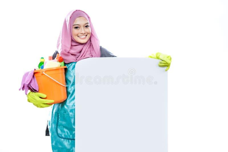 Hijab vestindo da jovem mulher que mantém uma cubeta completa da limpeza supl. fotografia de stock