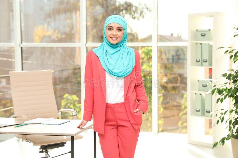 Hijab vestindo da mulher de negócios muçulmana moderna perto da tabela fotografia de stock