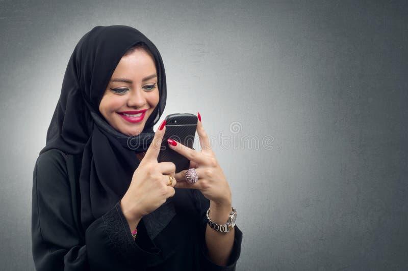 Hijab vestindo da senhora árabe usando seu móbil, imagens de stock