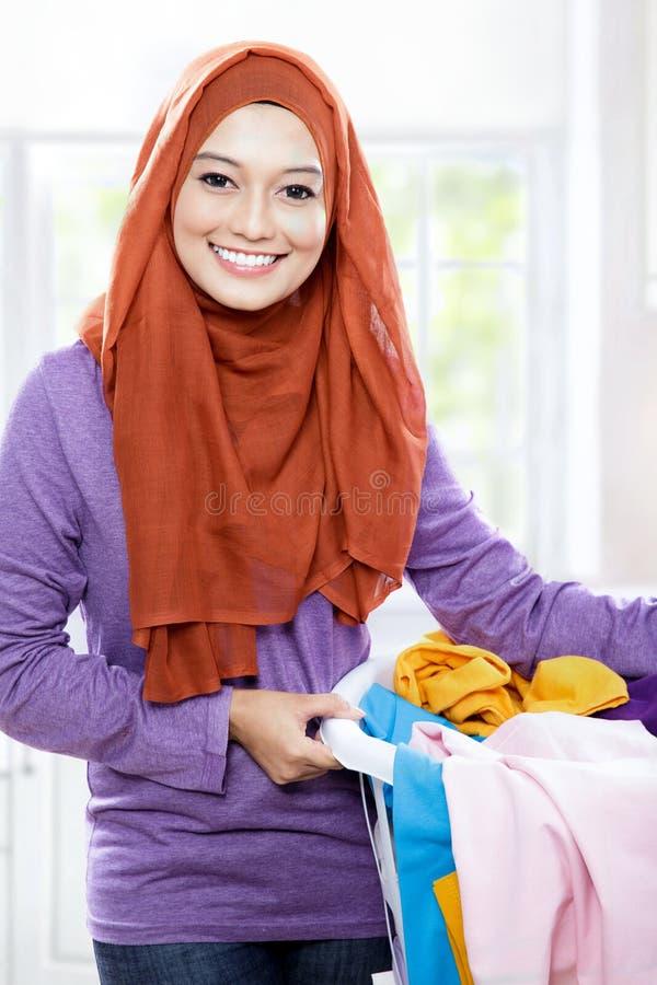 Hijab vestindo de sorriso bonito da mulher que guarda uma cesta de lavanderia foto de stock royalty free