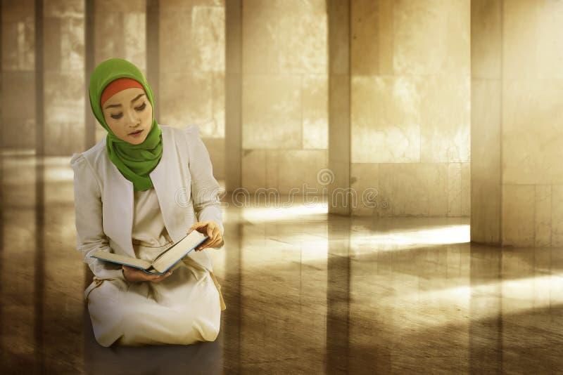 Hijab vestindo dos muçulmanos asiáticos da jovem mulher, lendo o koran fotos de stock royalty free