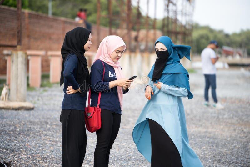 Hijabs flicka som kopplar av på sjösidan royaltyfri fotografi