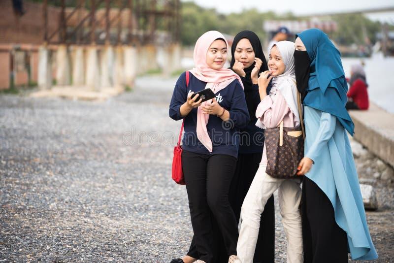 Hijabs flicka som kopplar av p? sj?sidan arkivfoto