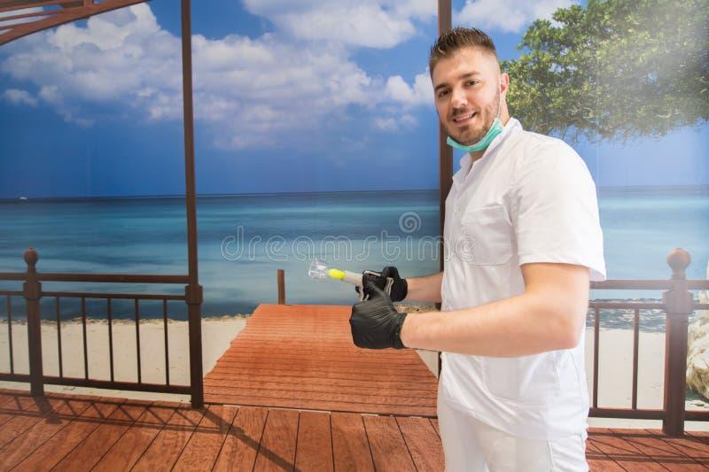 Hijama terapeut som poserar på strandbakgrunden Tumme upp vid terapeuten arkivfoto