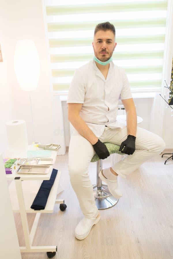 Hijama terapeut som sitter på stolen och poserar på massagerummet royaltyfria bilder
