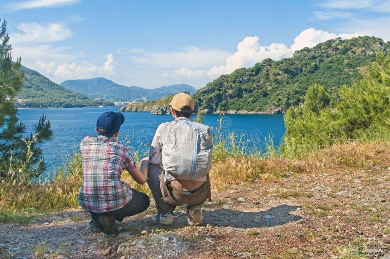 Hijo adolescente con su padre que mira la opinión del mar imagenes de archivo