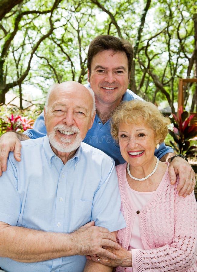 Hijo adulto y padres mayores imagenes de archivo