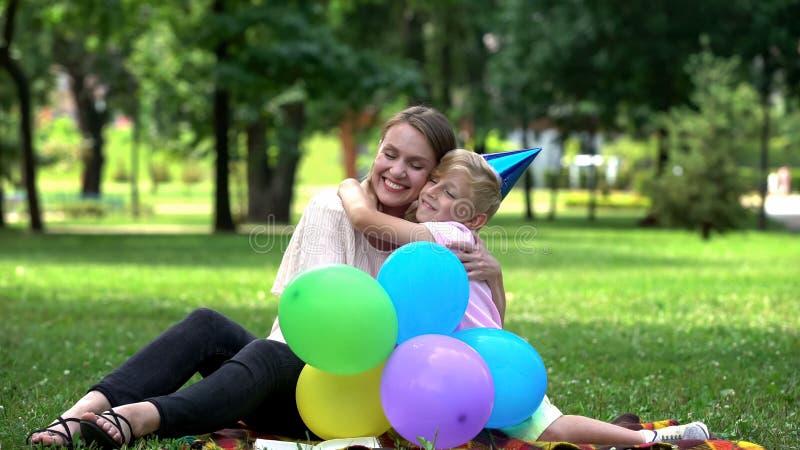 Hijo cariñoso que felicita a la mamá en cumpleaños, el solo parenting y el niño agradecido imagenes de archivo