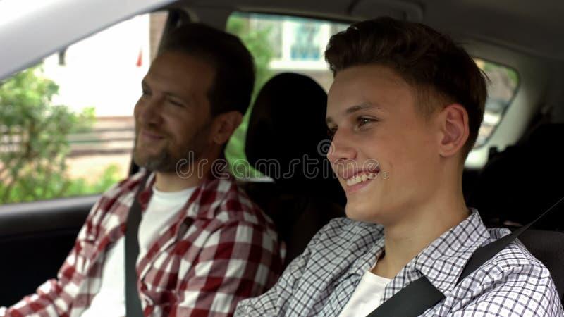 Hijo con el padre que prueba el nuevo coche comprado, papá que enseña al muchacho adolescente a conducir auto fotografía de archivo