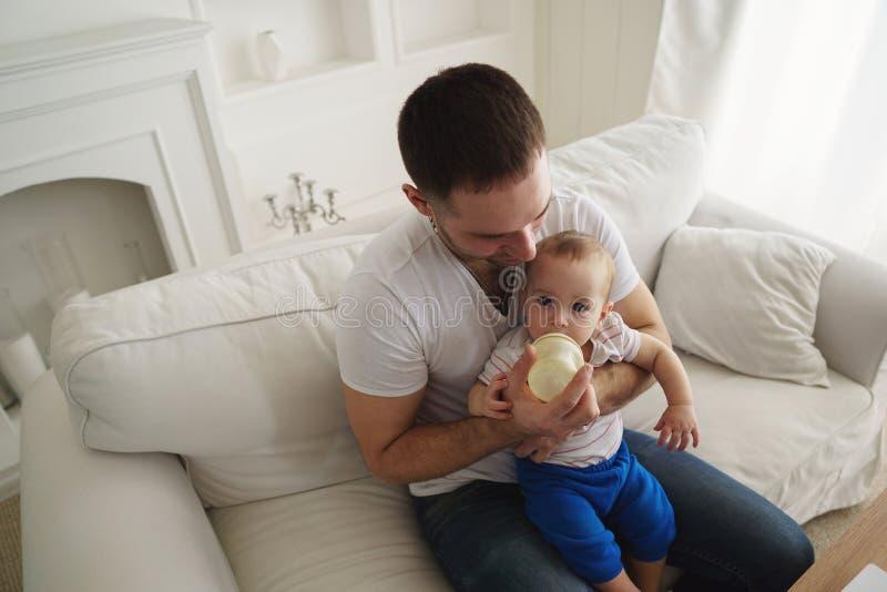 Hijo de alimentación del padre con preparado para bebés de la botella imagen de archivo libre de regalías