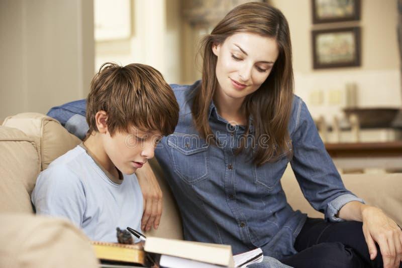 Hijo de ayuda de la madre con la preparación que se sienta en Sofa At Home imagen de archivo libre de regalías