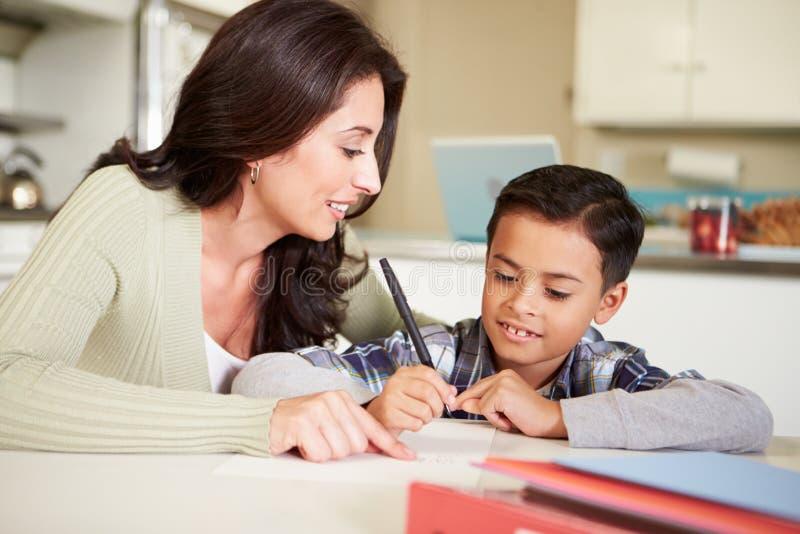 Hijo de ayuda de la madre hispánica con la preparación en la tabla foto de archivo