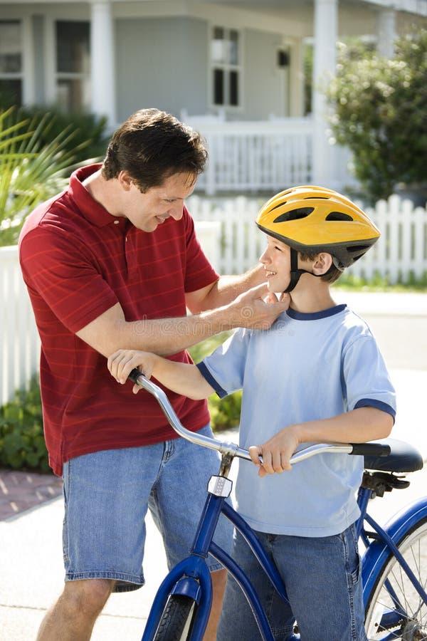 Hijo de ayuda del papá con el casco imagen de archivo