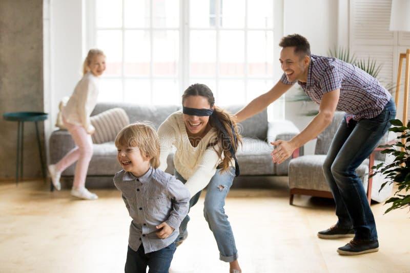 Hijo de cogida de la madre con los ojos vendados que juega escondite con el famil imagen de archivo libre de regalías