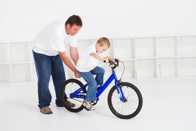 Hijo de enseñanza del padre a montar fotografía de archivo libre de regalías
