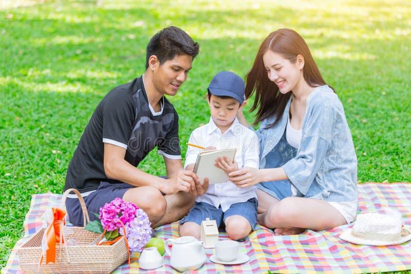 Hijo de enseñanza de la familia adolescente asiática mientras que comida campestre en el parque imagen de archivo