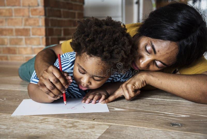 Hijo de enseñanza de la mamá cómo al dibujo foto de archivo libre de regalías