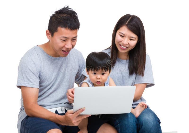 Hijo de la madre, del padre y del bebé que mira el ordenador portátil fotografía de archivo libre de regalías