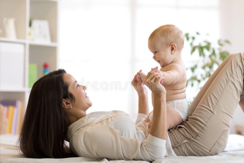 Hijo de la madre y del bebé que juega en dormitorio soleado Padre y niño que se relajan en casa Familia que se divierte junto imagen de archivo libre de regalías