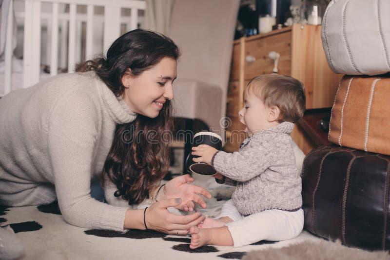 Hijo de la madre y del bebé que juega junto en casa Bebé de enseñanza a beber de la taza Forma de vida feliz de la familia fotografía de archivo libre de regalías