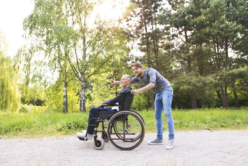 Hijo del inconformista que camina con el padre discapacitado en silla de ruedas en el parque fotos de archivo libres de regalías