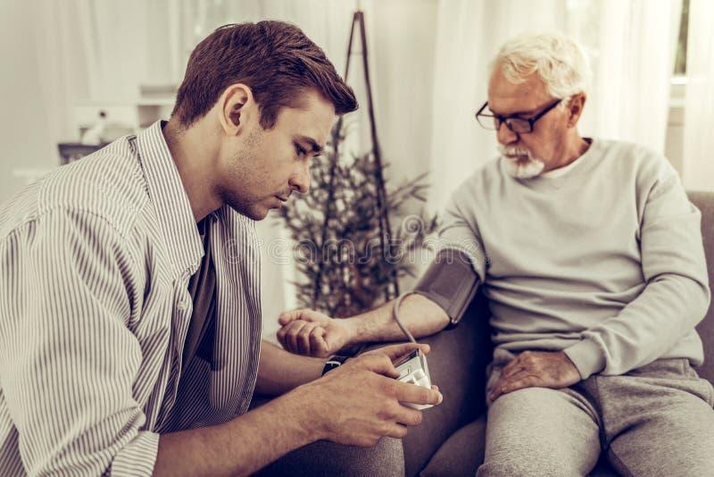 hijo del Joven-adulto que toma la presión arterial de su padre mayor imagen de archivo libre de regalías