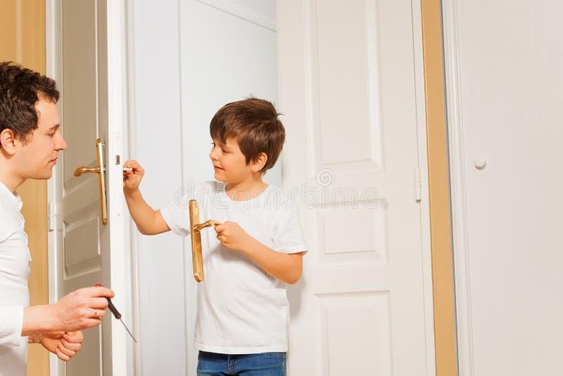 Hijo del padre y del niño que instala el tirador de puerta junto imagenes de archivo