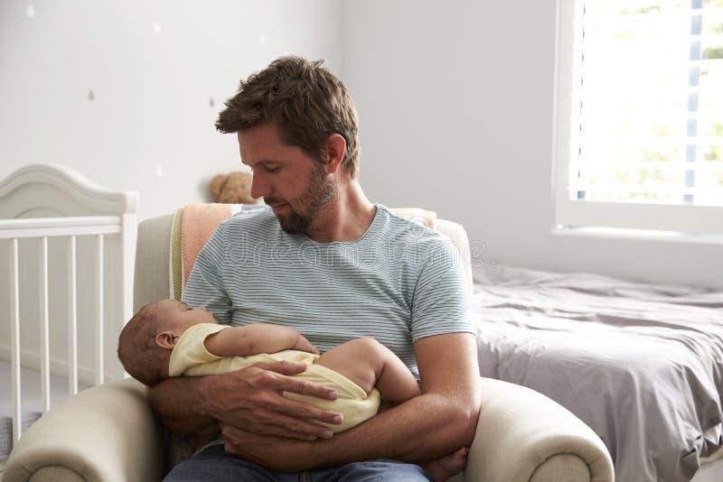 Hijo durmiente del bebé de los controles de la silla de Sitting In Nursery del padre fotografía de archivo