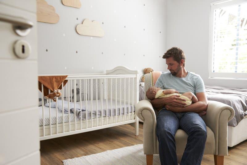 Hijo durmiente del bebé de los controles de la silla de Sitting In Nursery del padre imágenes de archivo libres de regalías